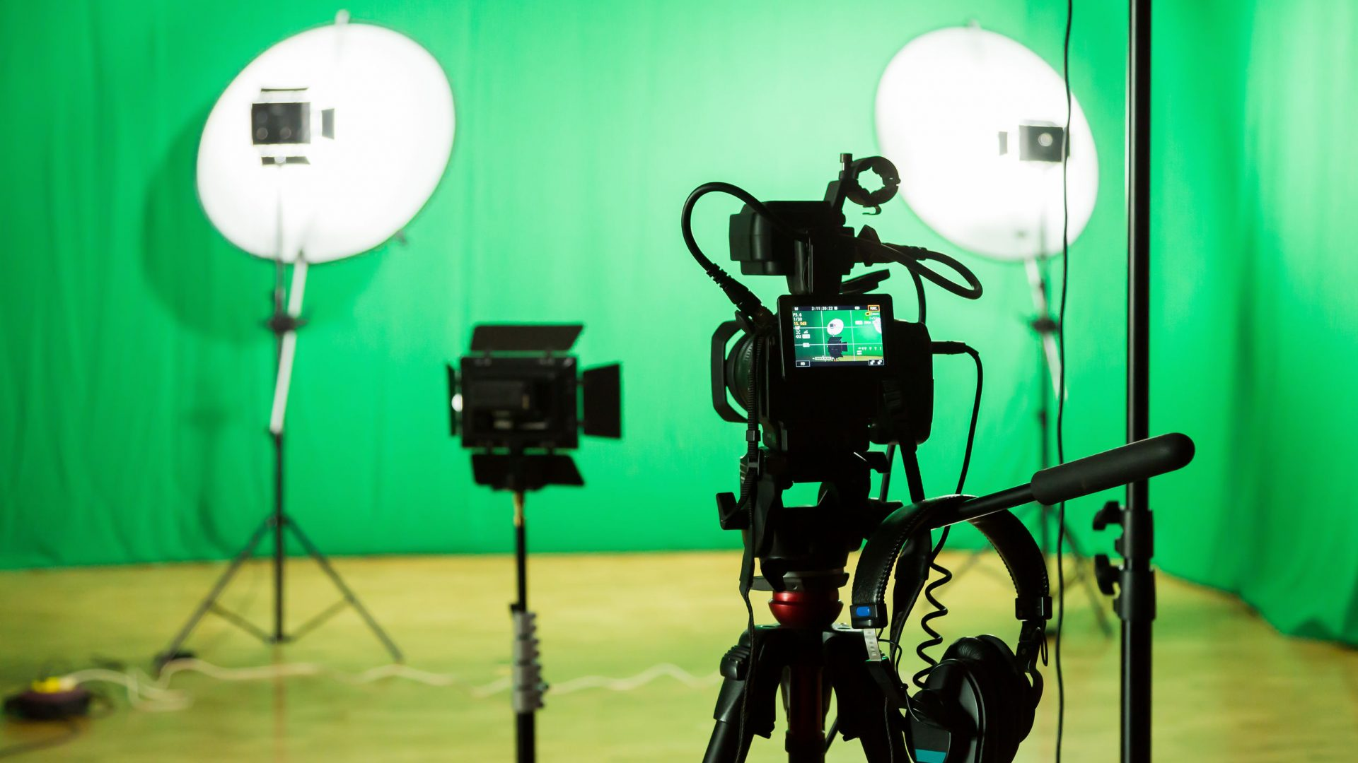 90315764 - studio for filming on a green background. the chroma key. lighting equipment in the studio. green screen.